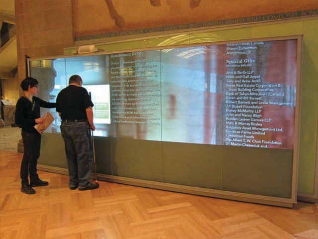 alison and user standing next to large glass encased touch screen kiosk on first floor of the ROM